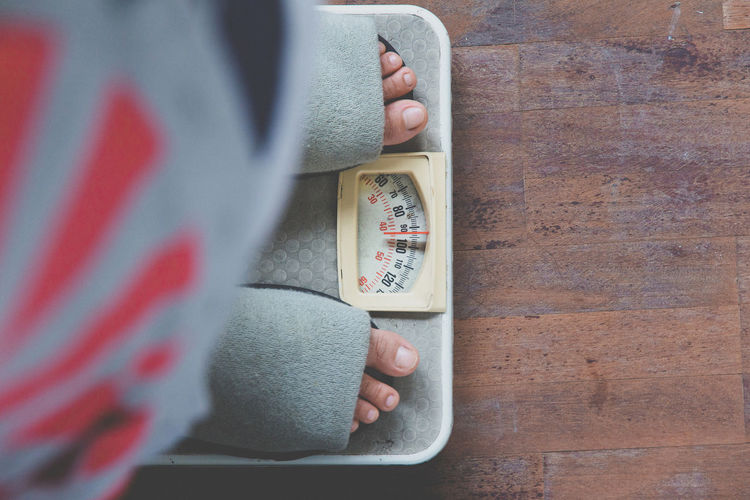 Low section of woman standing on weight scale