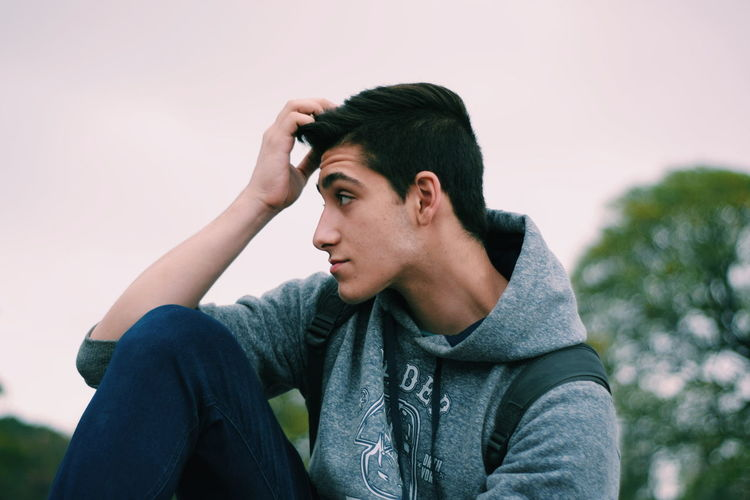 Portrait of young man looking away against sky