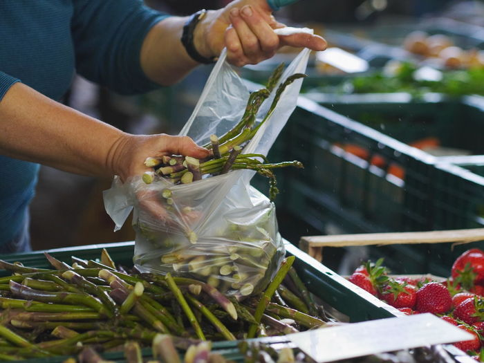 Midsection of woman holding asparagus in crate at market