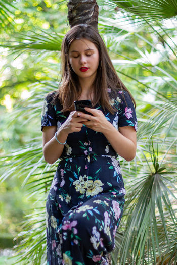 Young woman using phone while sitting on tree