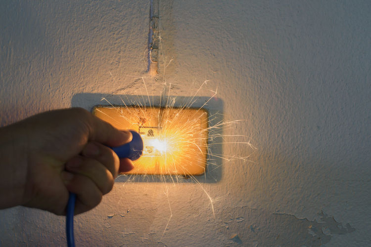 Cropped hand of person holding electric plug by sparkling outlet on wall