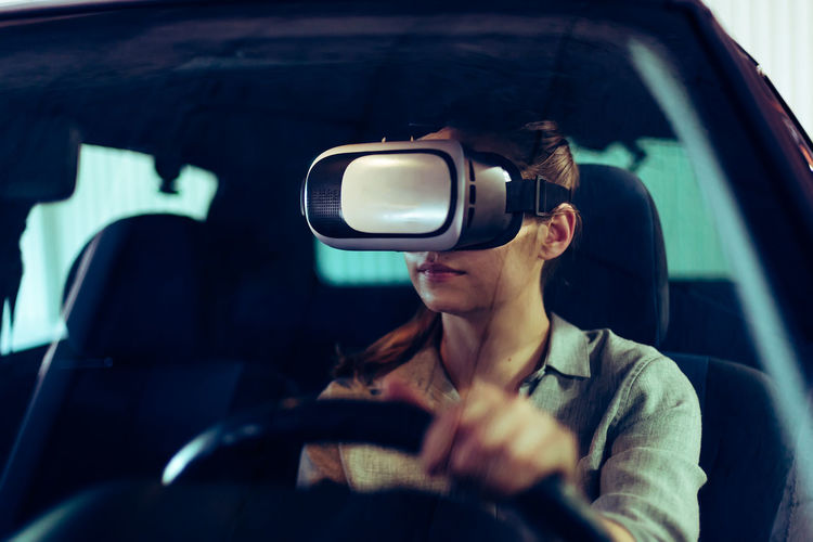Woman wearing 3d vr goggles, driving car in virtual space