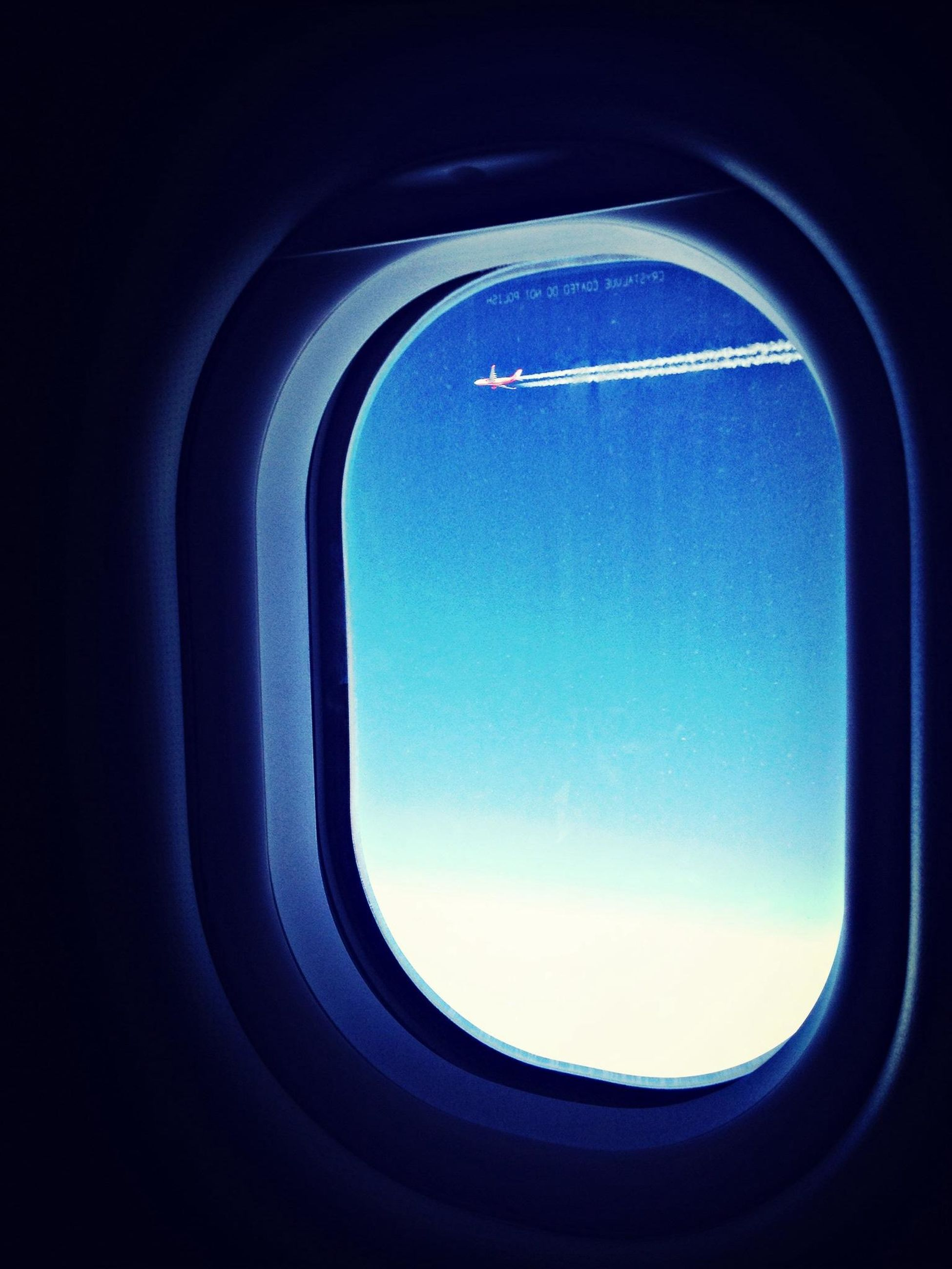 window, airplane, blue, indoors, transportation, vehicle interior, air vehicle, flying, transparent, glass - material, sky, low angle view, clear sky, mode of transport, part of, silhouette, mid-air, copy space, looking through window, journey