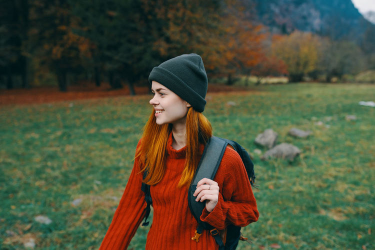 Young woman looking away while standing on field during autumn