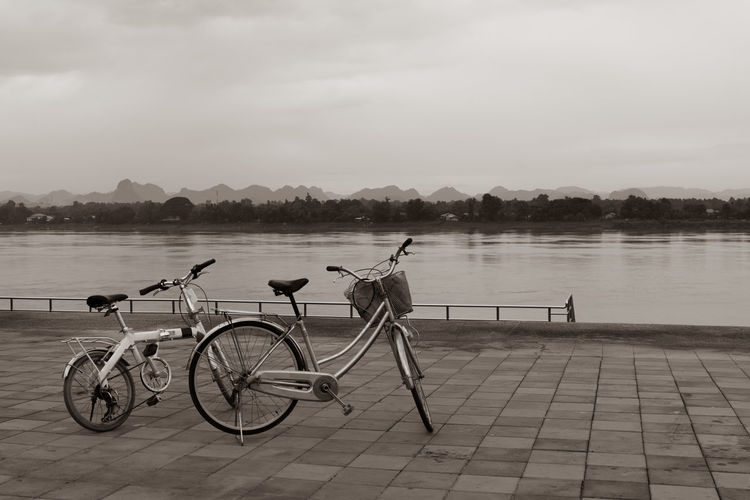 Bicycle on footpath by lake against sky