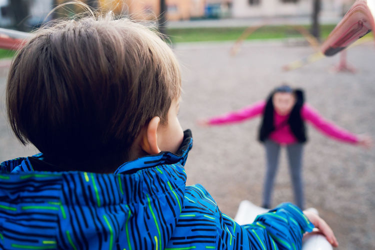 Rear view of son sliding while mother standing in background at park