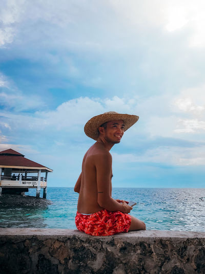 Dark tan gay guy wearing board shorts anda straw hat by the beach over a blue sky