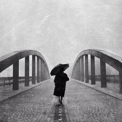 Person With Umbrella Walking On Bridge Against Clear Sky