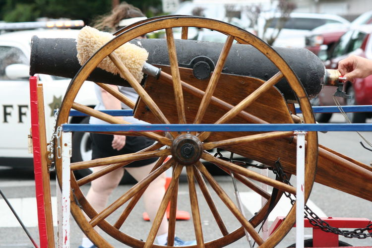 Cropped hand by cannon on street during fourth of july parade