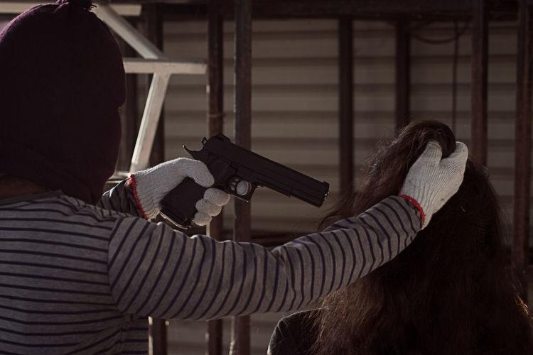 Rear view of burglar holding woman hair and handgun