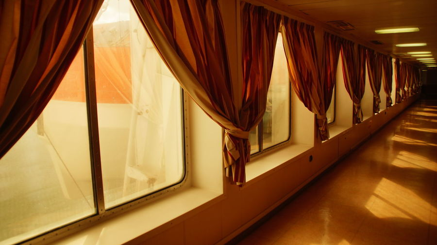 View of curtains on windows at corridor