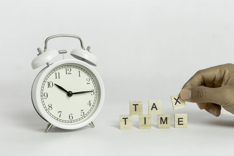 Close-up of hand holding clock over white background