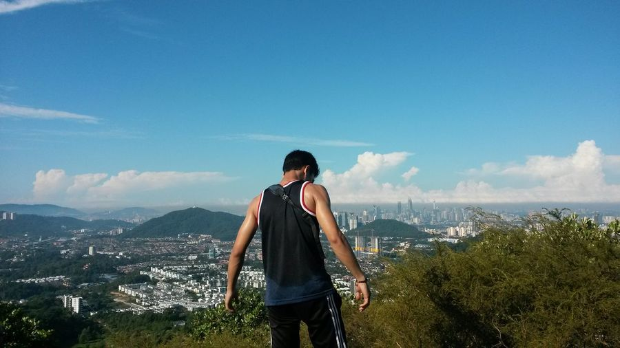 Rear view of man standing with city in background against blue sky