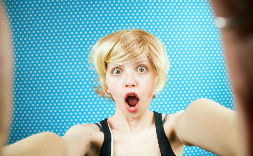 Portrait Of Shocked Woman Against Blue Curtain