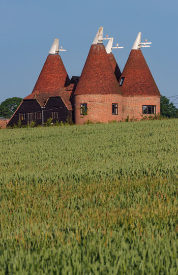 Oast house,Garden of England, Kent, England. Architecture Built Structure Building Exterior Building Field Plant House Land Sky Landscape Grass Rural Scene Growth Green Color No People Nature Agriculture Residential District Farm Day Outdoors Oast House Hops Travel Destinations Tourism Getty Images History Vivid International Village Tranquil Scene Wheat Field Church Tower
