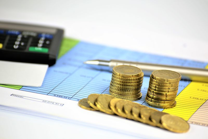 Close-up of coins with calculator on paper