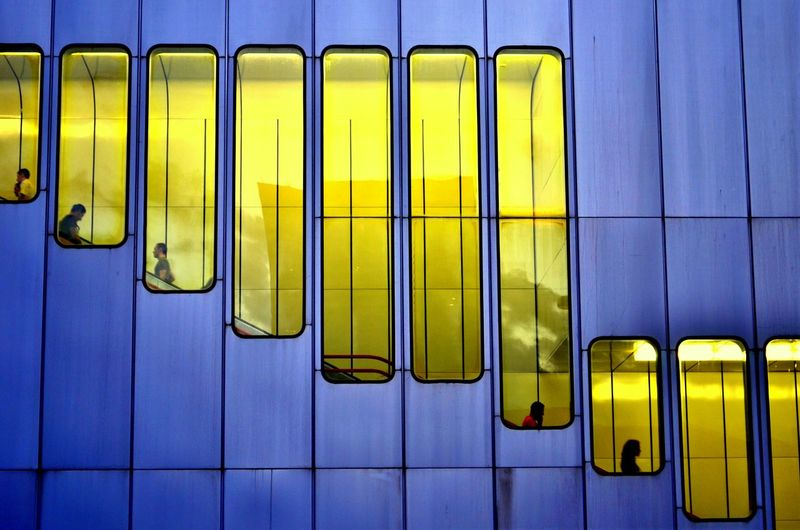 Low angle view of people on escalator seen through yellow windows