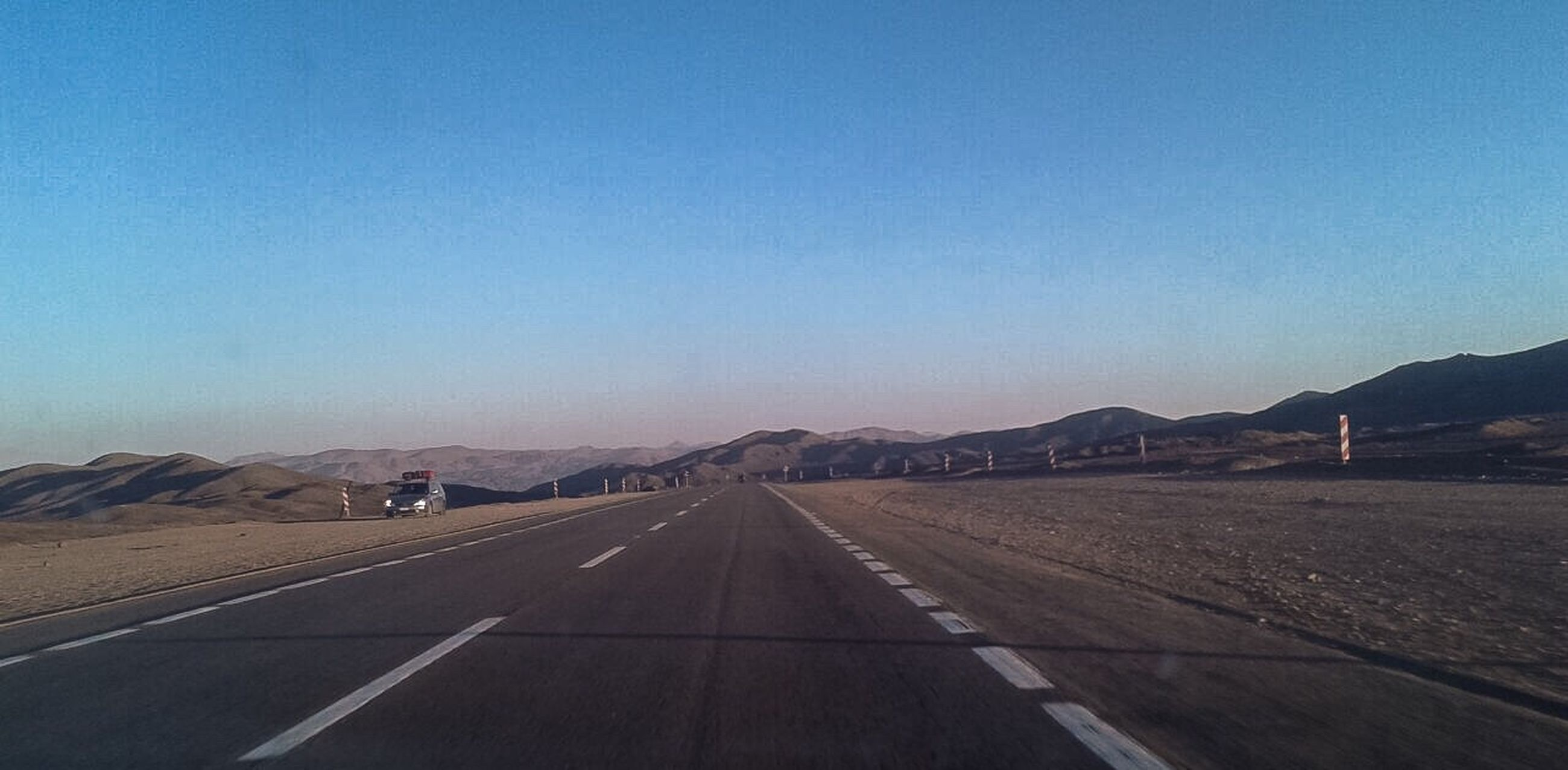 transportation, road, clear sky, road marking, mountain, empty, blue, copy space, the way forward, long, mountain range, country road, landscape, street, diminishing perspective, white line, vanishing point, tranquil scene, dividing line, day, surface level, tranquility, outdoors, solitude, scenics, nature, countryside