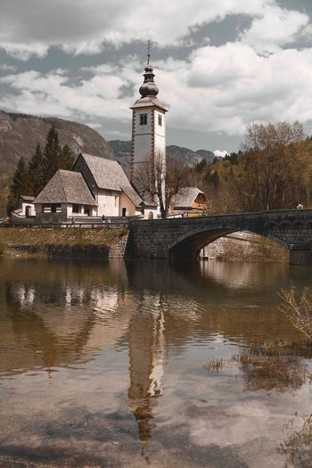 Still and peaceful. Slovenia Lake Bohinj Water Sky Cloud - Sky Built Structure Architecture Building Exterior Nature Reflection Tower No People Day Waterfront Building Outdoors Travel Destinations History Lake Tree