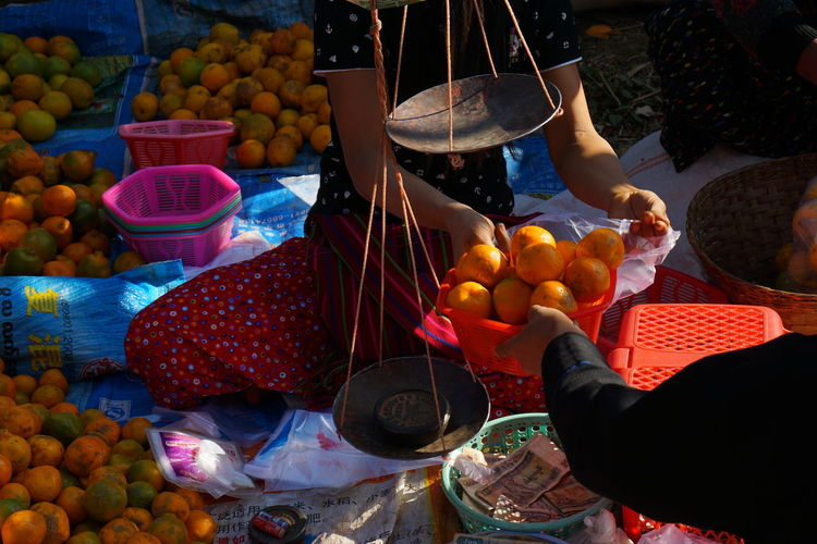Woman weighing fruits and selling at market stall
