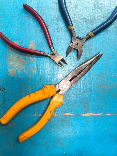 Pliers Industry Machinery Engineering Equipment Wallpaper Backgrounds Red Blue Yellow Primary Colors EyeEm Selects Blue No People Table Indoors  Still Life Wood - Material High Angle View Metal Work Tool Creativity Connection Art And Craft Design Equipment Pliers Shape Tool Close-up Directly Above