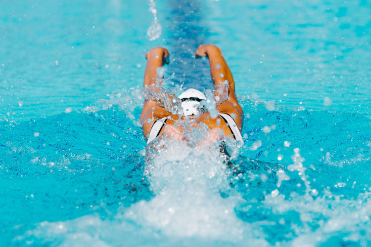 Female Swimmer on Training in the Swimming Pool Swimmer Female Water Style Butterfly Sport Young Pool Competition Swimwear Athlete Goggles Training Swim Competitive Healthy People Active Cap Swimming Swimming Pool Energy Exercise Professional Woman Strength Adult Muscular Lifestyle Activity Race Action Winner Motion Health Skill  Caucasian White Exercising Healthy Lifestyle Sports Training Beautiful Outdoors Color Image Blue One Person Splashing Day