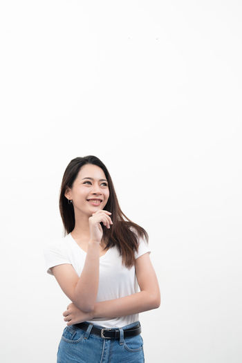 Beautiful Woman Casual Clothing Copy Space Front View Hair Hairstyle Happiness Holding Indoors  Long Hair Looking At Camera One Person Portrait Smiling Standing Studio Shot Tank Top White Background Young Adult Young Women