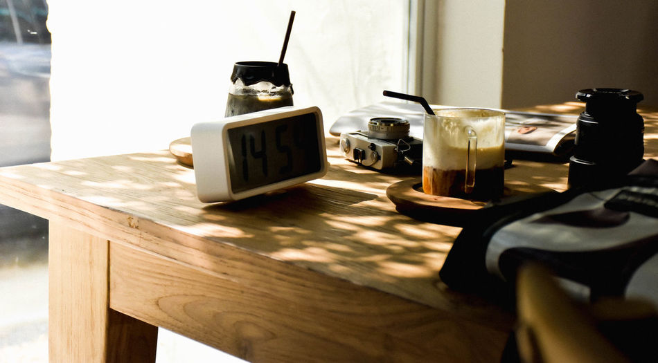 Close-up of digital clock and coffee cup on table