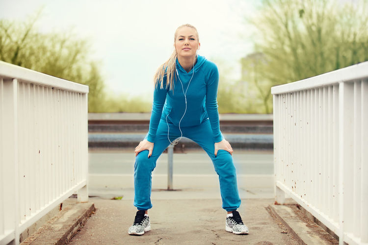 Full Length Portrait Of Young Woman Doing Warm Up Exercises On Footpath