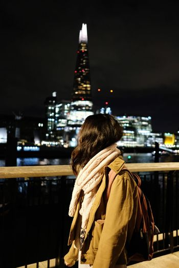 Rear view of woman against illuminated buildings in city at night