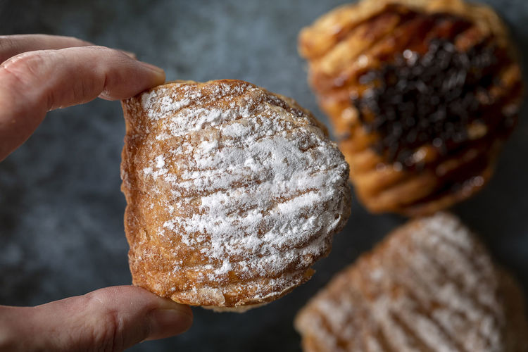 Two fingers of a female hand hold a sweet crescent with powdered sugar.