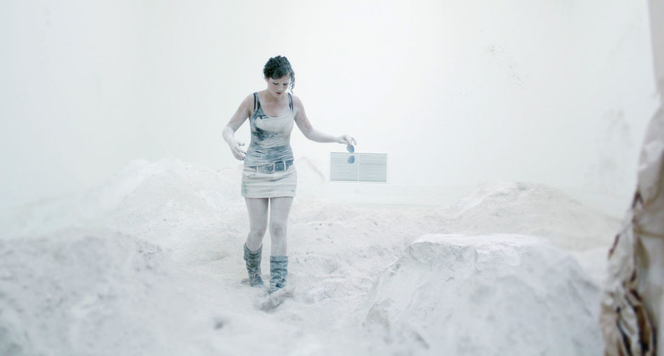 Full length of messy artist walking amidst powdered plaster at workshop
