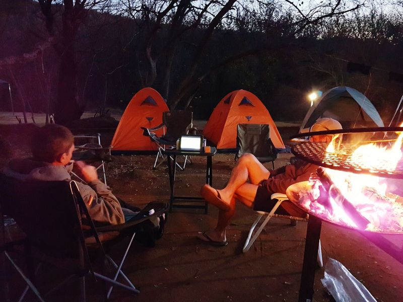 Watching the game Adult Men Two People Sitting Campinglife Campfire Tablet Device Watching The Game Rugby On The Tablet Technology