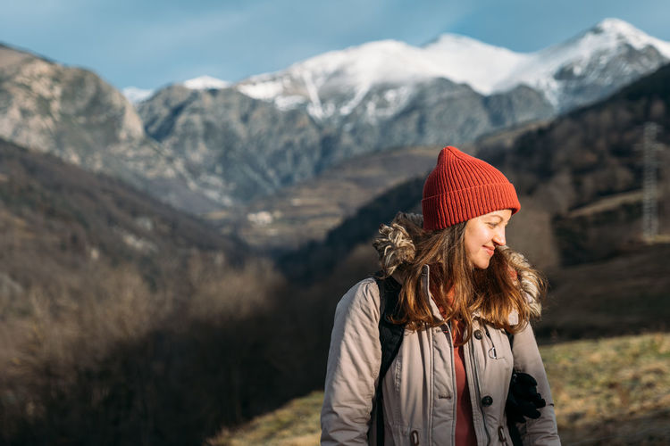Smiling traveler at the snowy mountains. happy woman in red cap warming up and enjoying the sunlight