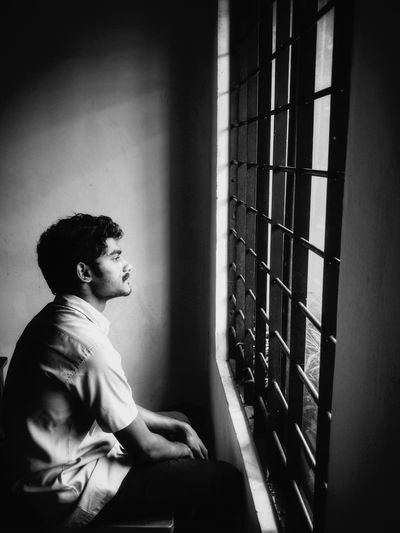 Side view of young man looking through window against wall at home