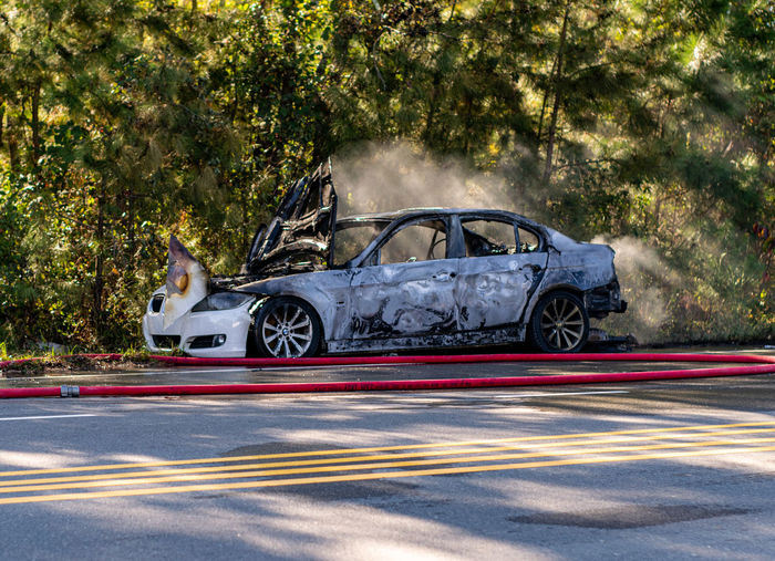 Burned out wreck of car still smoking while firefighters were still on scene in creedmor, nc