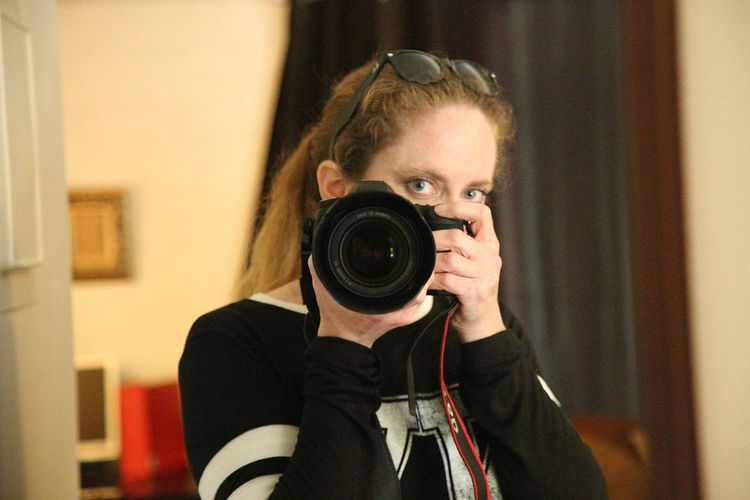 Portrait of woman holding camera reflecting on mirror at home