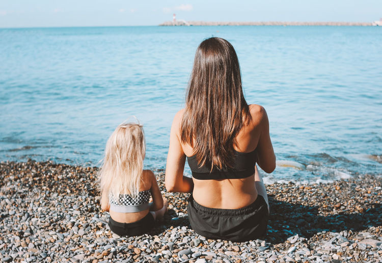Rear view of mother and daughter sitting at beach
