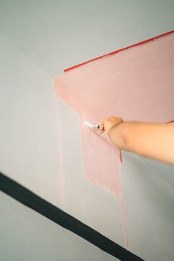 Low angle view of woman painting wall in home