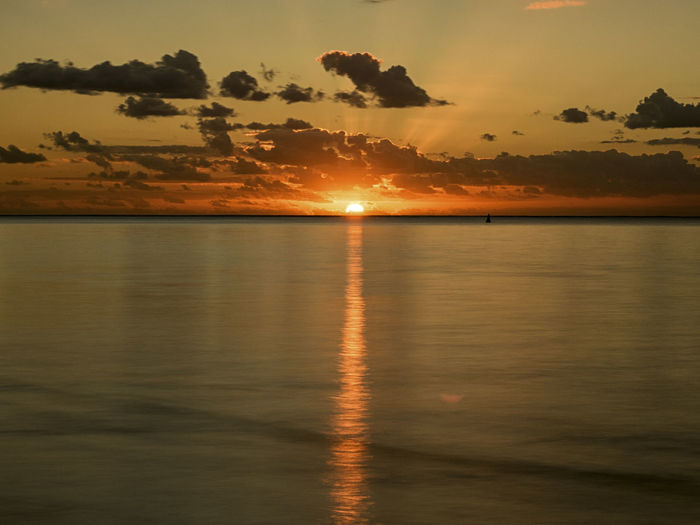 Reflection Water Sun Sunset Nature Sky Silhouette Travel Sunlight Romantic Tranquility Ocean Vacations Mauritius Scenics Beauty In Nature No People Orange Color Travel Destinations Tranquil Scene Horizon Over Water Cloud - Sky Copy Space Idyllic Raising