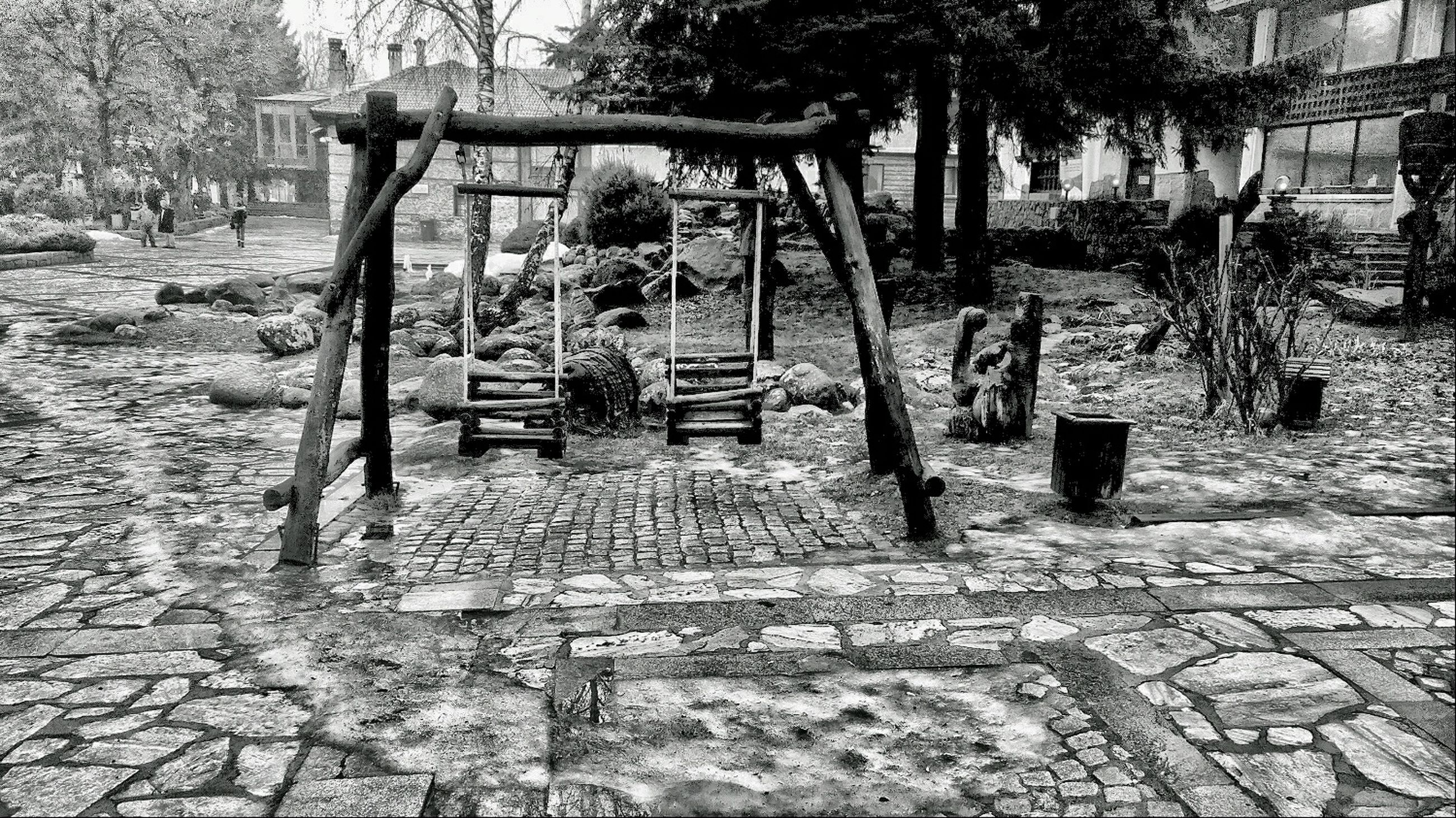 tree, chair, absence, bench, empty, day, building exterior, built structure, outdoors, cobblestone, large group of objects, sunlight, architecture, wood - material, no people, old, stack, abundance, seat, footpath