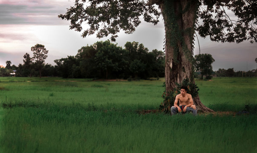 Shirtless man sitting on grassy land against sky