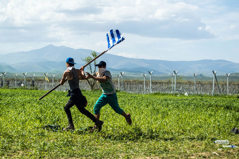 Refugees with greek flag running on grassy field