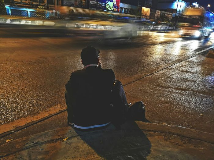 Rear view of man sitting on road at night