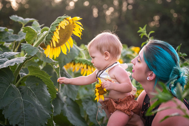 Mother carrying daughter by yellow flowering plants
