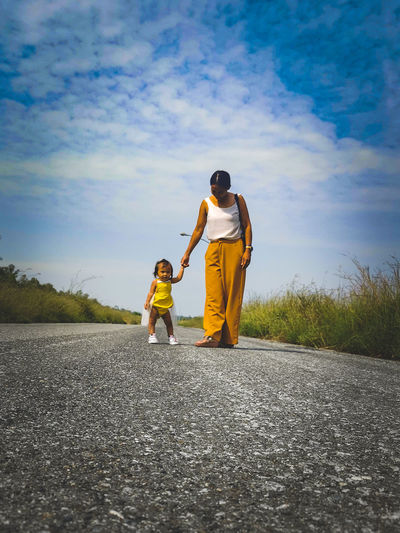 Rear view of mother and daughter standing on riverbank against sky