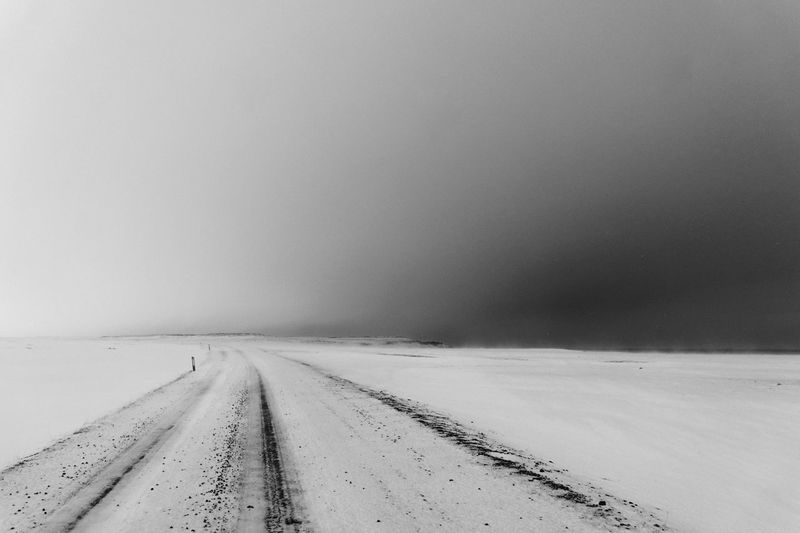 Empty road amidst snow covered field against clear sky during winter