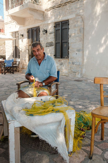 Babis, a local fisherman and one of 400 inhabitants of the island - Halki, Greece, 2018 Aegean Sea Work Adult Candid Emotion Fisherman Greece Happiness Leisure Activity Lifestyles Mature Adult Mature Men Men Portrait Sailor Seat Sitting Streetphotography