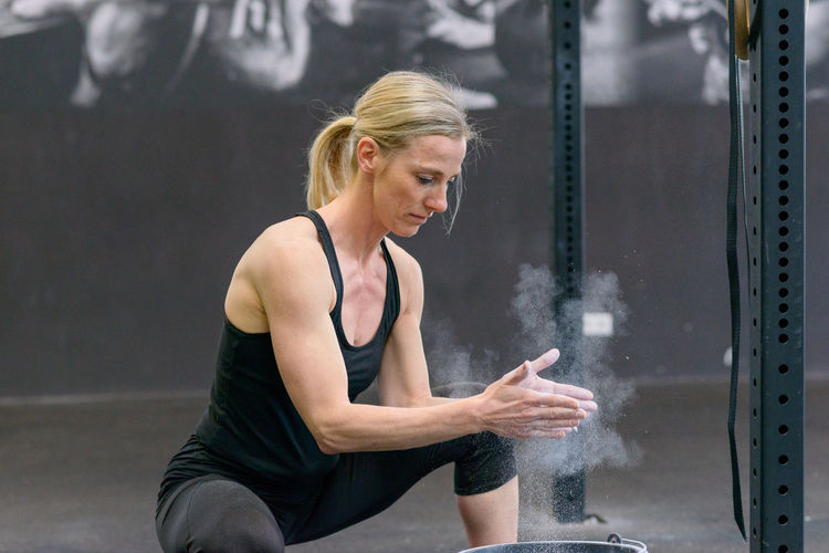 Mature woman applying sports chalk in gym