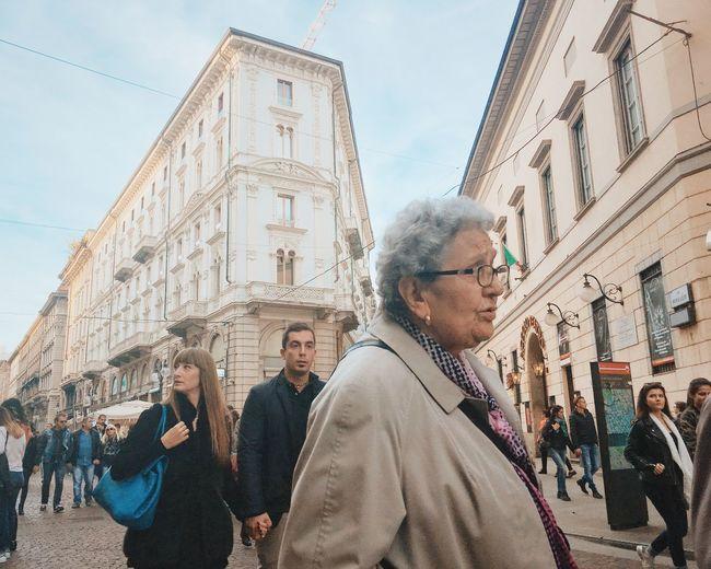 People on street in front of buildings against sky